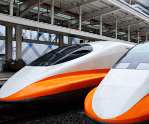 two high speed bullet trains parked in station