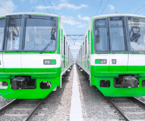 two refurbished electric commuter trains parked in a station side by side